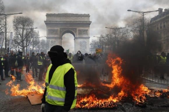 Parigi in fiamme, scontro sugli Champs-Élysées, gente presa a sassi e palazzi in fiamme